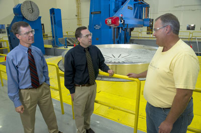 As an adapter ring designed for the Space Launch System is machined at Marshall, Brent Gaddes, left, Patrick Hull and Myron Tapscott discuss the intricate design work going into the SLS.